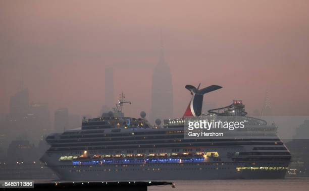 The Carnival Sunshine cruise ship passes by midotwn Manhattan and the Empire State Building in New York City on September 16 as seen from Jersey City...