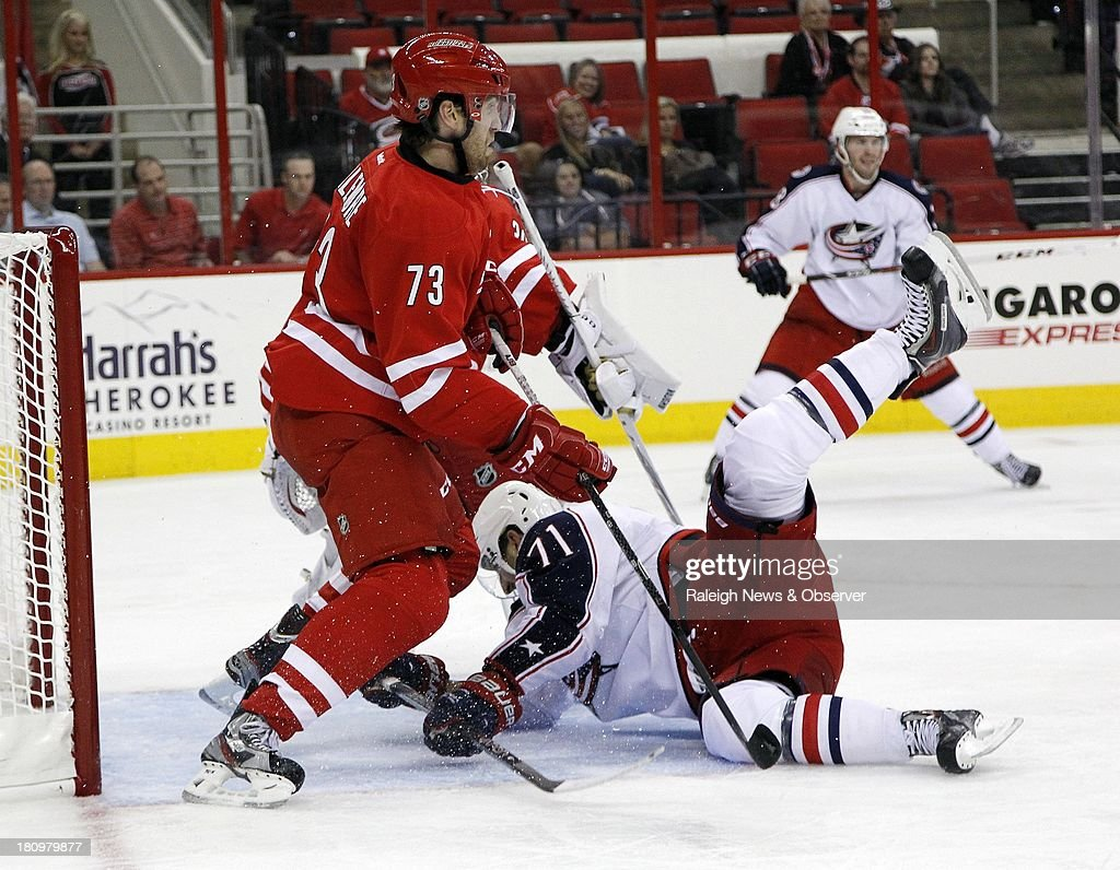 The Carolina Hurricanes' Brett Bellemore (73) defends the goal as the Columbus Blue Jackets' Nick Foligno (71) crashes in during the second period at the PNC Arena in Raleigh, North Carolina on Wednesday, September 18, 2013. Columbus won, 5-4.