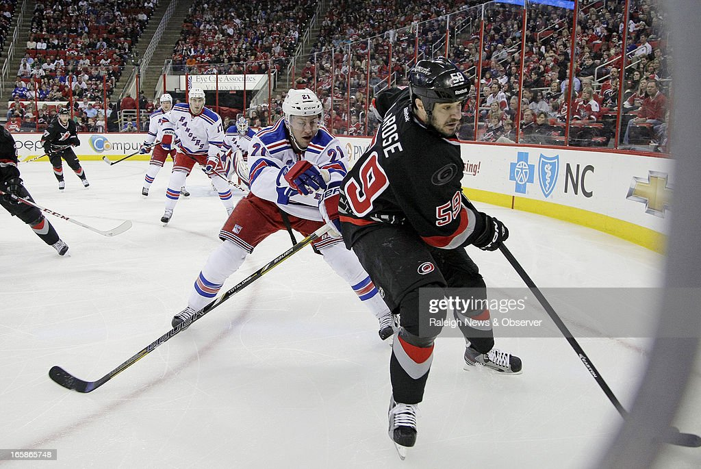 The Carolina Hurricanes' Chad LaRose (59) battles against the New York Rangers' Derek Stepan (21) for the puck along the boards during the first period at the PNC Arena in Raleigh, North Carolina, on Saturday, April 6, 2013.