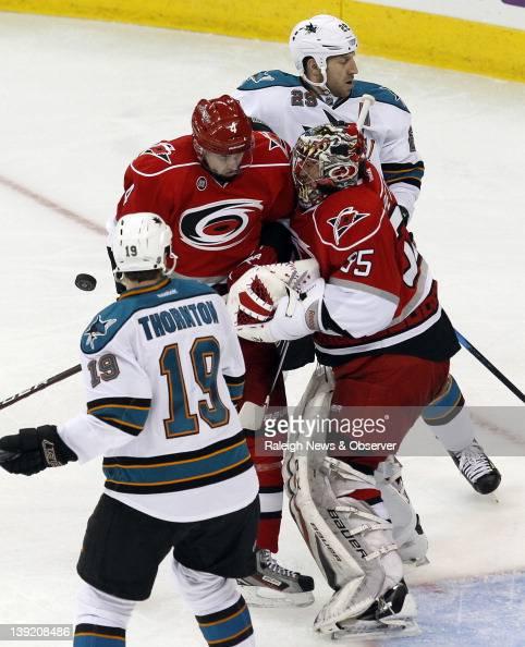The Carolina Hurricanes' Jamie McBain and goalie Justin Peters battle the San Jose Sharks' Joe Thornton and Ryane Clowe during the second period at...