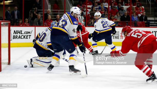 The Carolina Hurricanes' Jeff Skinner shoots against the St Louis Blues' Carter Hutton Jordan Schmaltz and Alexander Steen during the first period at...
