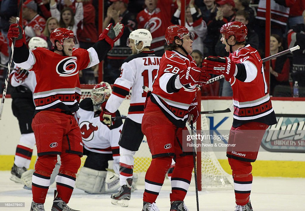 The Carolina Hurricanes' Jiri Tlusty, left, and Eric Staal congratulate teammate Alexander Semin (28) after he scored against the New Jersey Devils' Johan Hedberg (1) and Travis Zajac (19) during the first period at the PNC Arena in Raleigh, North Carolina, on Saturday, March 9, 2013.