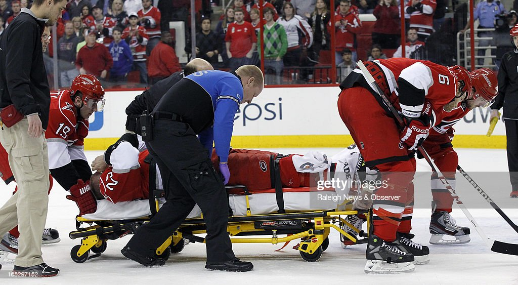The Carolina Hurricanes' Joni Pitkanen is taken out on stretcher with the help of teammates Jiri Tlusty (19) and Tim Gleason (6) during the second period against the Washington Capitals at the PNC Arena in Raleigh, North Carolina, on Tuesday, April 2, 2013. Pitkanen was injured on a race to the puck for an icing call.