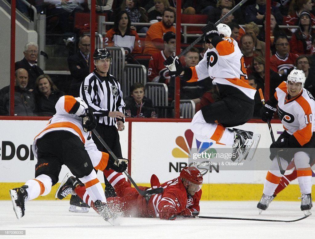 The Carolina Hurricanes' Manny Malhotra (22) dives to block as the Philadelphia Flyers'' Mark Streit (32) fires a shot while Jakub Voracek (93) jumps out of the way during the first period at the PNC Arena in Raleigh, North Carolina, on Tuesday, November 5, 2013.
