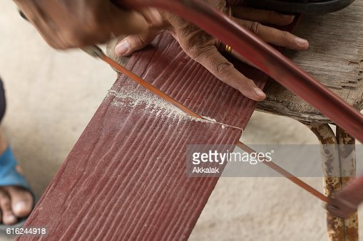 The carpenter is sawing the brown plank : Stock Photo