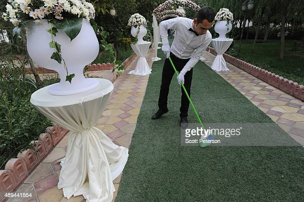 The carpet is swept by a whitegloved server as Iranian families take part in a luxury wedding with mixed dancing and removal of headscarves at a...