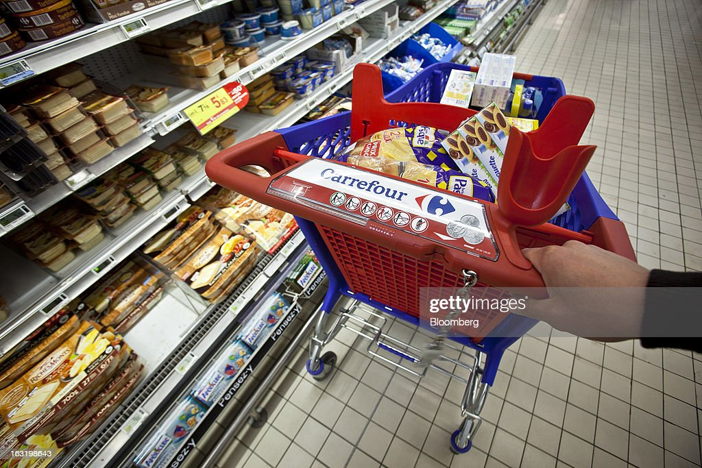The Carrefour logo is seen on a customer's shopping cart in this arranged photograph taken in the chilled food aisle of a Carrefour SA supermarket in Portet sur Garonne, near Toulouse, France, on Tuesday, March 5, 2013. Carrefour's stock has risen 47 percent since Georges Plassat's arrival as chief executive officer, partially offsetting a 71 percent decline in the preceding five years. Photographer: Balint Porneczi/Bloomberg via Getty Images