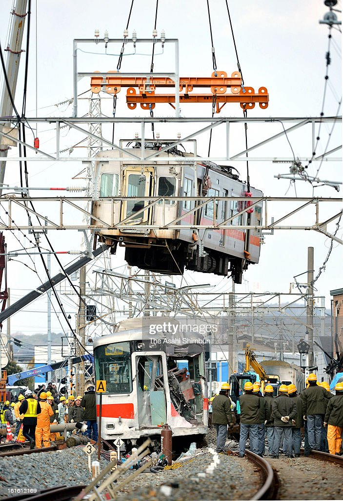 The carriage of the derailed Sanyo Electric Railway Co. train is lifted to remove from the accident site a day after a collision with a truck at Arai Station on February 13, 2013 in Takasago, Hyogo, Japan. Fifteen people injured by the accident. A driver of the truck was arrested.