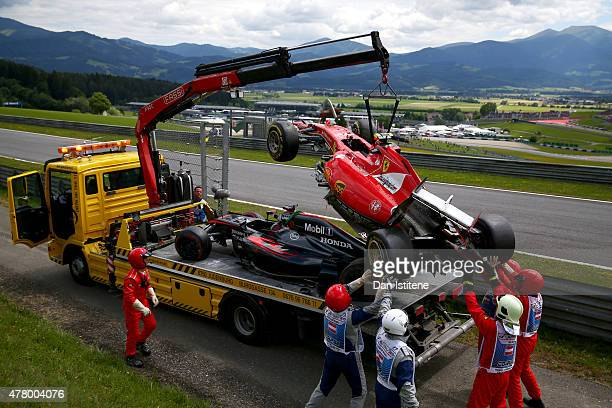 The cars of Fernando Alonso of Spain and McLaren Honda and Kimi Raikkonen of Finland and Ferrari wait to be returned to the garages after crashing...