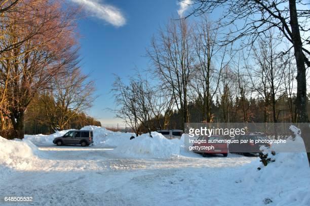 The cars parking between heap of snow under evening light