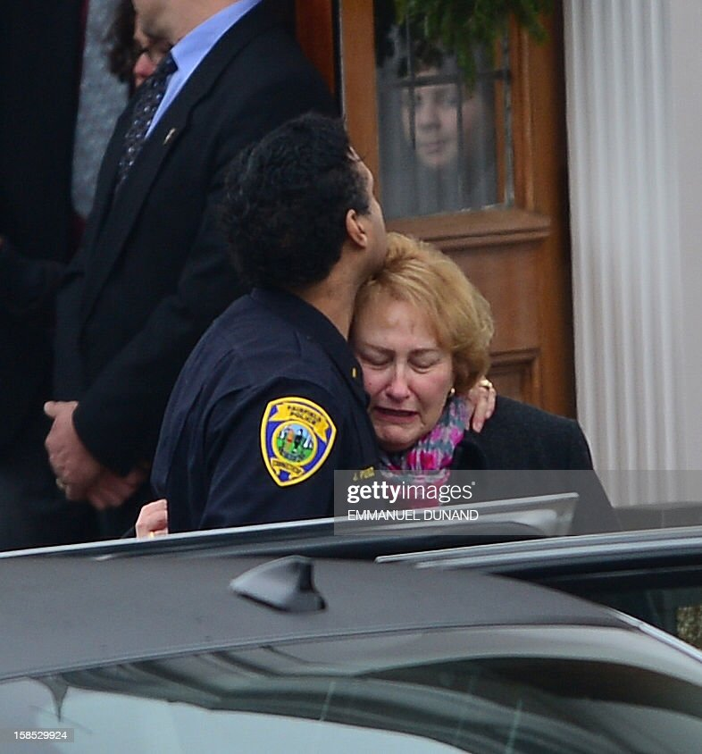 The casket of James Mattioli, 6 leaves Saint Rose of Lima Church as mourners gather on December 18, 2012 in Newtown, Connecticut after his funeral. Most children in Newtown returned to classes Tuesday for the first time since last week's massacre, but survivors of the shooting stayed at home and their school remained a crime scene. In a thin drizzle, yellow school buses once again rolled through the Connecticut town, where some 5,400 children are enrolled. AFP PHOTO/EMMANUEL DUNAND