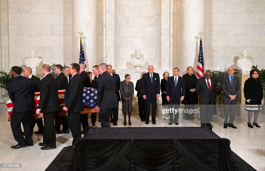 The casket of late Supreme Court Justice Antonin Scalia is carried into the Great Hall of the Supreme Court for a private ceremony on February 19, 2016 in Washington, DC. Supreme Court Justices from back left Counselor to the Chief Justice Jeffrey Minear, and Supreme Court Justices Elena Kagan, Samuel Anthony Alito, Jr., Ruth Bader Ginsburg, Anthony M. Kennedy, Chief Justice John G. Roberts, Jr., Clarence Thomas, Stephen G. Breyer, and Sonia Sotomayor. Justice Scalia will lie in repose at the high court where visitors can pay their respects.