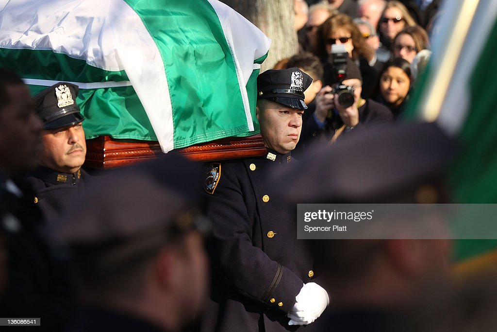 The casket of police officer Peter Figoski is brought into a church during the funeral for the New York City police officer who was killed last week...