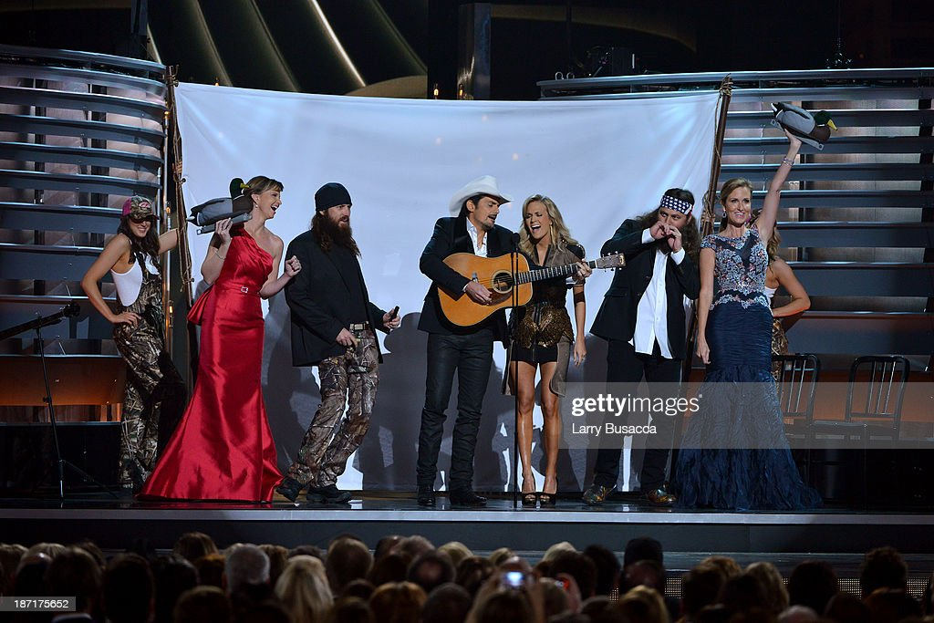 The cast of 'Duck Dynasty' onstage with Hosts Brad Paisley and Carrie Underwood during the 47th annual CMA Awards at the Bridgestone Arena on November 6, 2013 in Nashville, Tennessee.