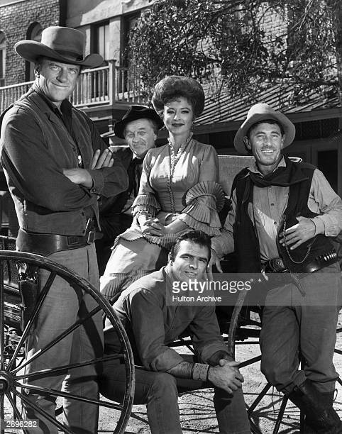 The cast of 'Gunsmoke' poses around a wagon in a promotional portrait for the Western television series LR Actors James Arness Milburn Stone Amanda...