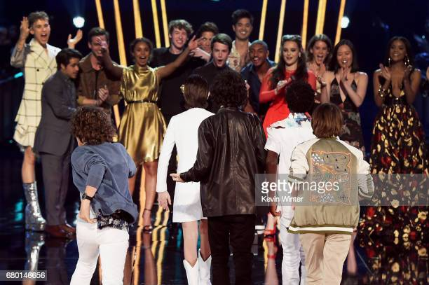 The cast of 'Stranger Things' walks onstage to accept Show of the Year from the cast of '13 Reasons Why' during the 2017 MTV Movie And TV Awards at...