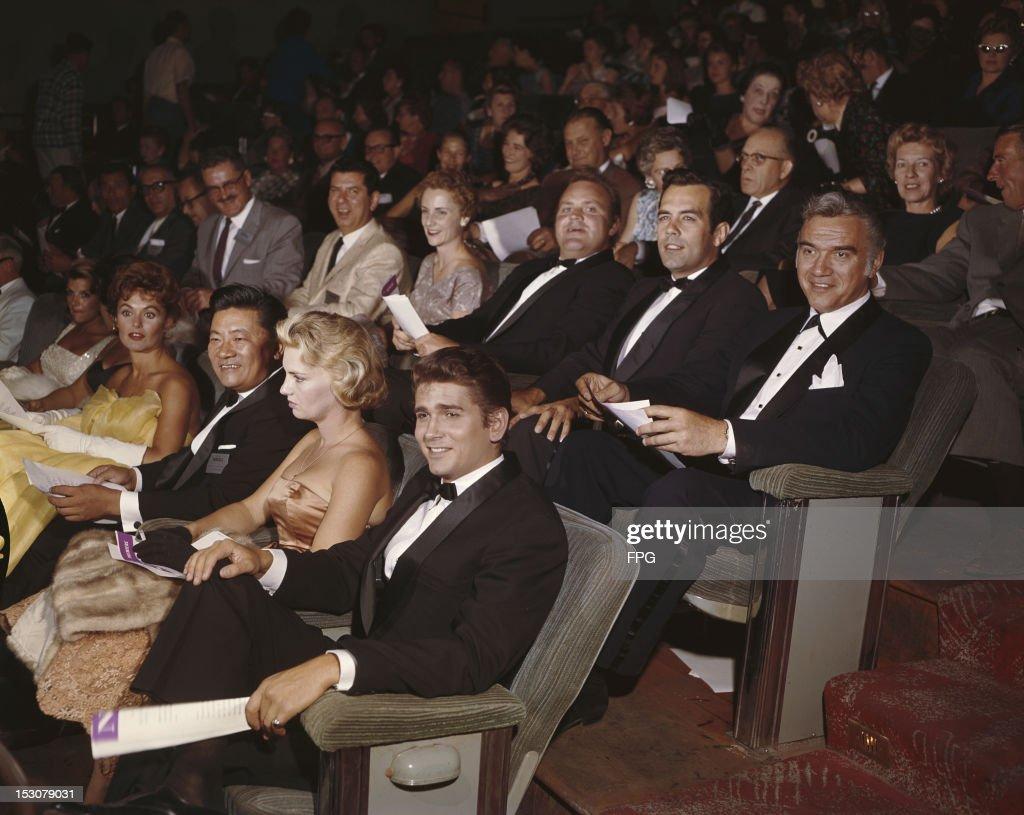 The cast of the television series 'Bonanza' attend an award ceremony, circa 1960. Victor Sen Yung and Michael Landon sit in front of (left to right) Dan Blocker, Pernell Roberts and Lorne Greene.