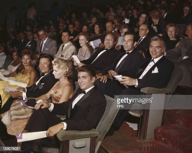 The cast of the television series 'Bonanza' attend an award ceremony circa 1960 Victor Sen Yung and Michael Landon sit in front of Dan Blocker...