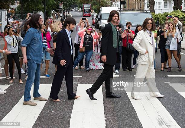 The cast of the West End Beatles show 'Let It Be' cross the zebra crossing outside Abbey Road Studios during a photocall to celebrate The Beatles...