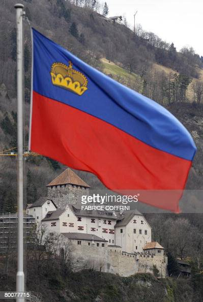 The Castel of Vaduz home of the Liechtenstein princely family is pictured behind a Liechtenstein's flag on March 1 2008 in Vaduz Liechtenstein whose...