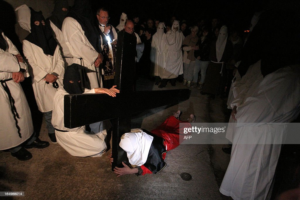 The 'catenacciu,' a hooded and chained penitent bearing a cross, lays on the ground as part of a Good Friday procession commemorating the crucifixion of Jesus Christ in the village of Bisinchi, on the French mediterranean Island of Corsica, on March 30, 2013. AFP PHOTO / PASCAL POCHARD-CASABIANCA
