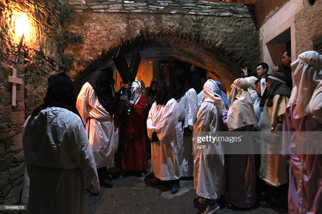 The 'catenacciu,' a hooded and chained penitent carries a cross, as part of a Good Friday procession commemorating the crucifixion of Jesus Christ in the village of Bisinchi, on the French mediterranean Island of Corsica, on March 30, 2013.
