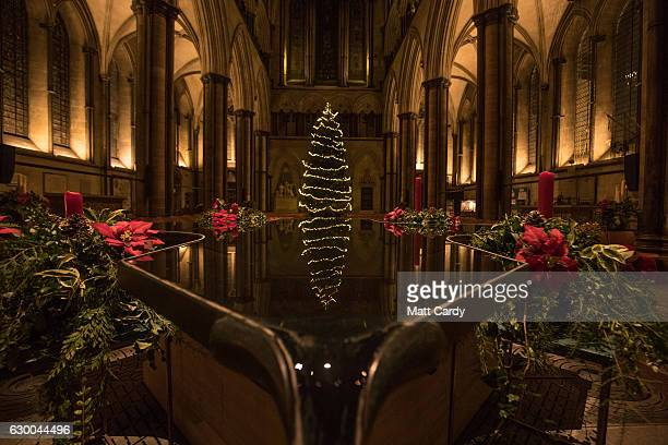 The Cathedral's Christmas tree is seen reflected in the font during a dress rehearsal of A Winter's Trail a new promenade drama being held at...