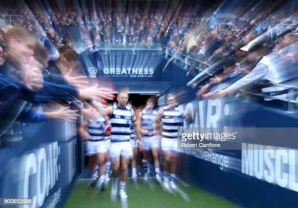 The Cats make their way out for the round 14 AFL match between the Geelong Cats and the Fremantle Dockers at Simonds Stadium on June 25 2017 in...