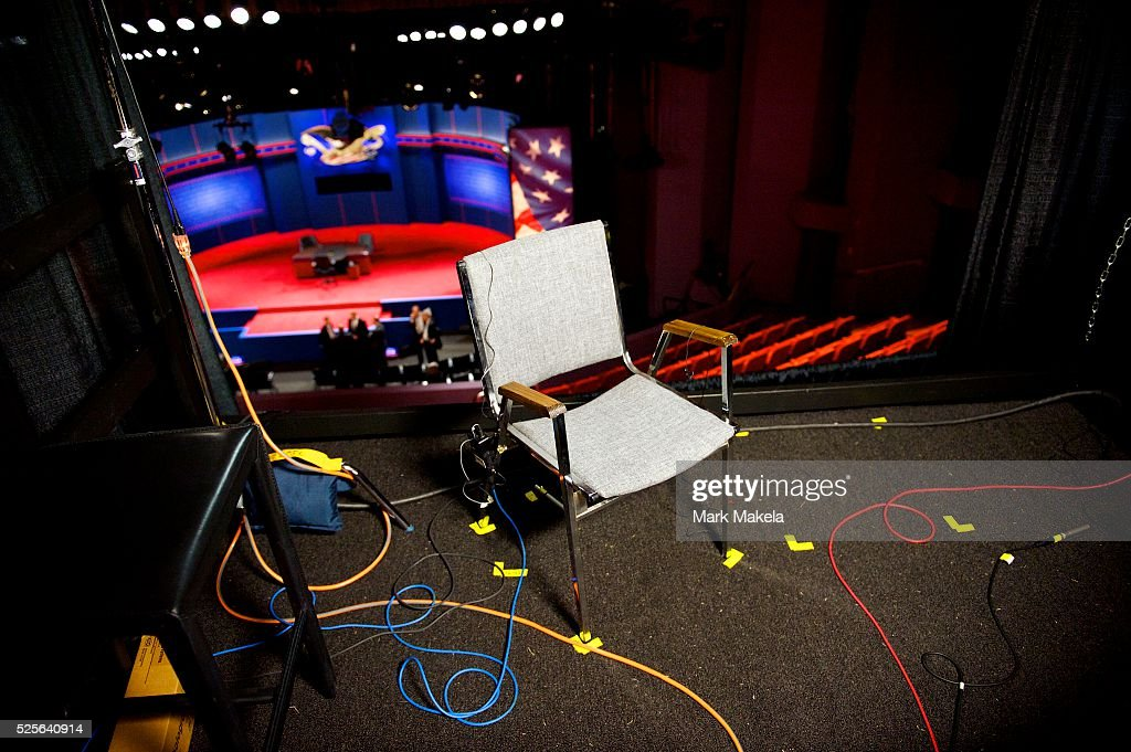 The CBS news broadcast booth features numerous pieces of color tape to mark chair positions in a temporary auditorium balcony television studio...