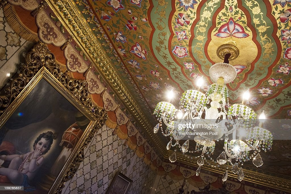 The ceiling and chandeliers inside the Palace of Gold were created by devotees. A painting of Krishna hangs on the wall. The ceiling, painted with gold leaf, took about six months to complete.