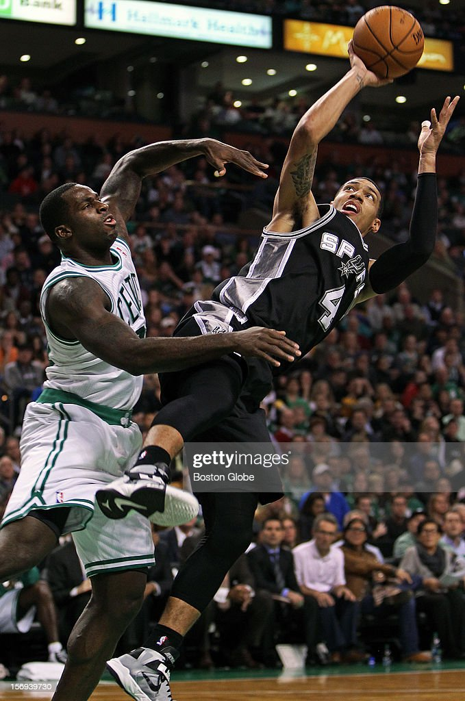 The Celtics' Brandon Bass, left, defends on a first half drive to the hoop by the Spurs Danny Green, right as the Boston Celtics hosted the San Antonio Spurs in a regular season NBA game at the TD Garden.