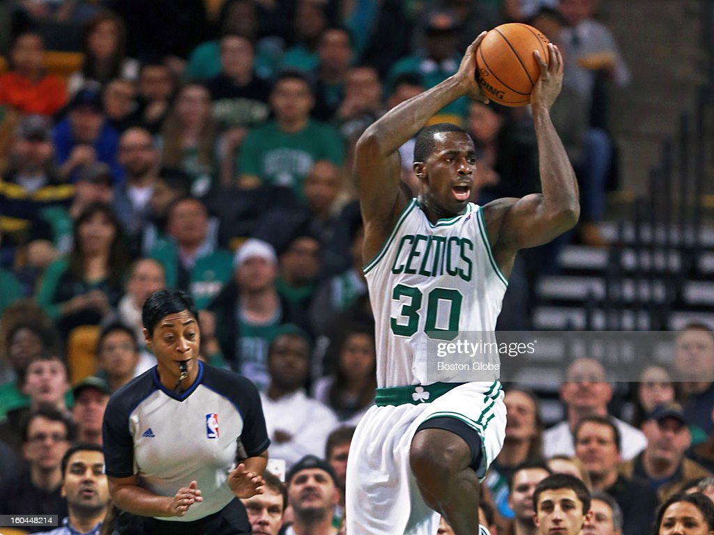 The Celtics' Brandon Bass tries to maintain his balance to avoid tripping over a fallen Francisco Garcia of the Kings as he looks for an outlet pass in the first half while referee Violet Palmer looks on. The Boston Celtics hosted the Sacramento Kings in an NBA regular season game at the TD Garden.