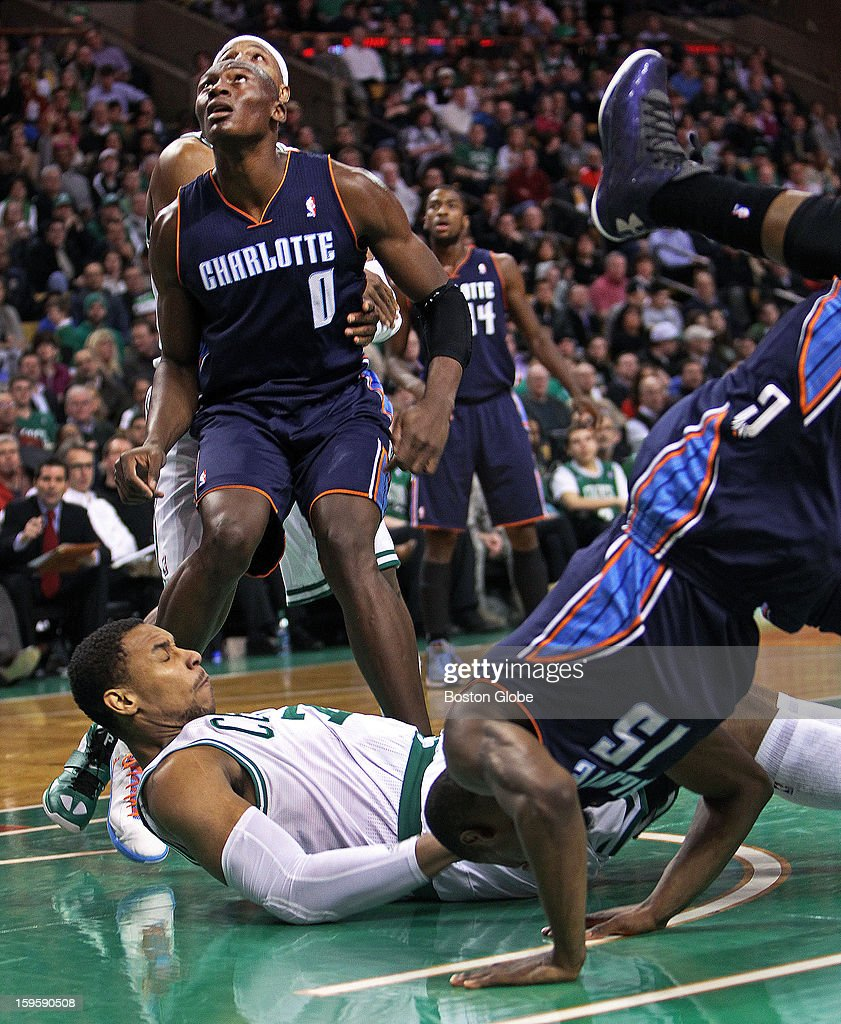The Celtics' Jared Sullinger hits the floor as he draws a charge against the Bobcats' Kemba Walker (#15) in the third quarter. He then braces himself for a possible landing spot for Charlotte's Bismack Biyombo (#0), who follows the ball as it bounces away. The Boston Celtics hosted the Charlotte Bobcats in a regular season NBA game at TD Garden.