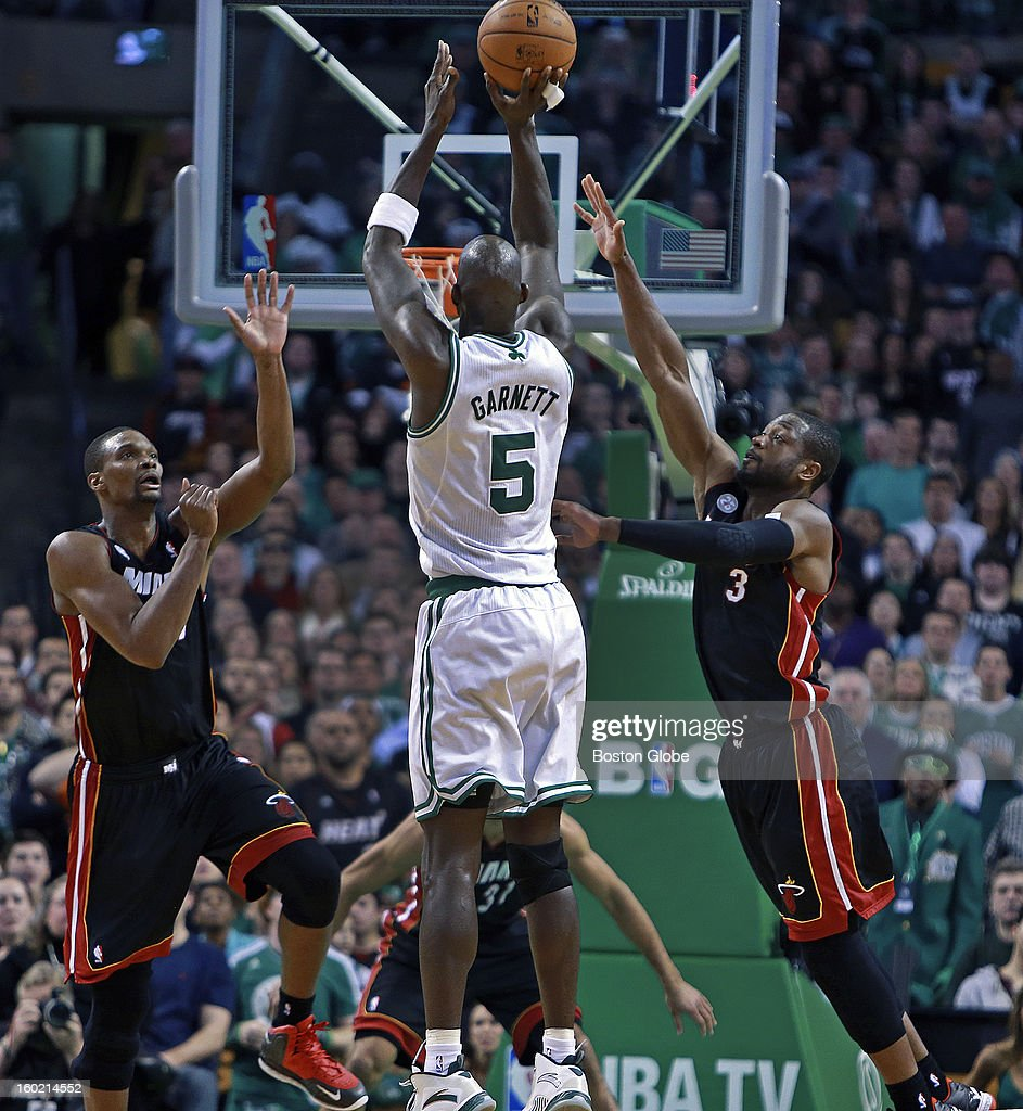 The Celtics' Kevin Garnett (#5) hit what was at the time a huge shot over the twin defense of Miami's Chris Bosh, left, and Dwyane Wade, right, that put Boston ahead 85-81 late in regulation, but the Heat would tie it up on a big three pointer from LeBron James, not pictured, to send the game into the first of two overtime periods as the Boston Celtics hosted the Miami Heat in an NBA regular season game at the TD Garden.