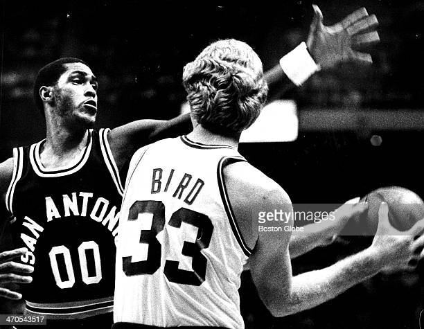 The Celtics' Larry Bird has a tough time passing off as he is guarded closely by the Spurs' Johnny Moore as the San Antonio Spurs play the Boston...