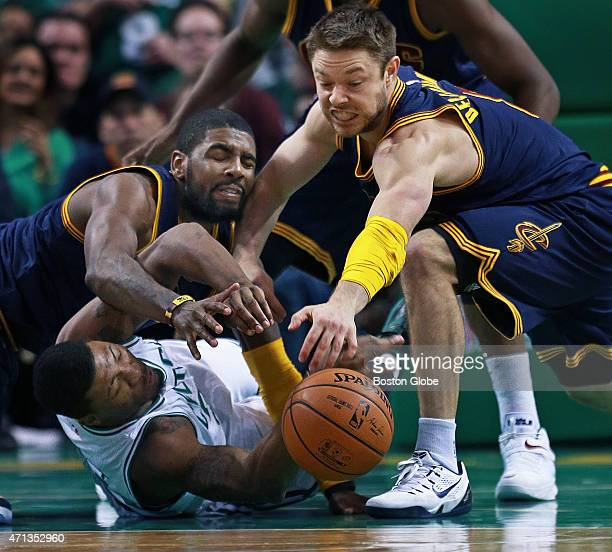 The Celtics' Marcus Smart finds himself down and out as Cleveland's Kyrie Irving and Matthew Dellavedova battle him for a second half loose ball The...