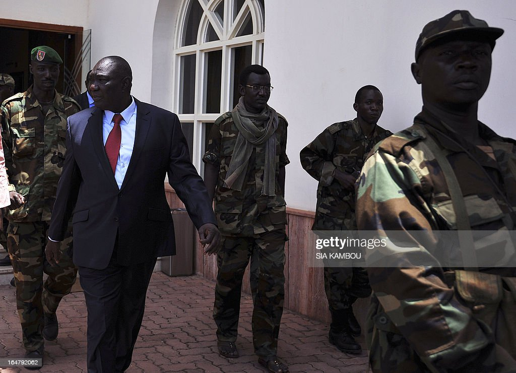 The Central African Republic's new strongman, Michel Djotodia (L) leaves a meeting with Central African Seleka rebels, whose coalition on March 24, 2013 seized control of Bangui in a rapid-fire weekend assault that forced President Francois Bozize into exile, and Central African Republic Army Forces (FACA) soldiers on March 28, 2013 in Bangui. New rebel authorities in the Central African Republic struggled to restore order in the coup-hit capital on Thursday as the UN warned tens of thousands of people faced going hungry after days of looting.