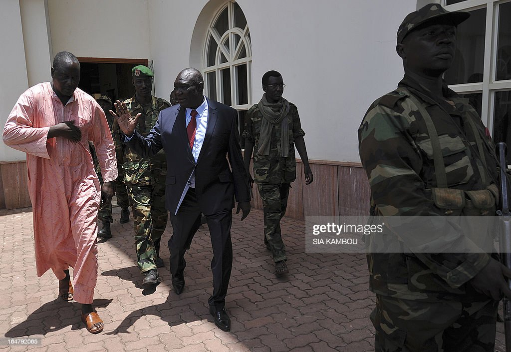The Central African Republic's new strongman, Michel Djotodia (C) leaves a meeting with Central African Seleka rebels, whose coalition on March 24, 2013 seized control of Bangui in a rapid-fire weekend assault that forced President Francois Bozize into exile, and Central African Republic Army Forces (FACA) soldiers on March 28, 2013 in Bangui. New rebel authorities in the Central African Republic struggled to restore order in the coup-hit capital on Thursday as the UN warned tens of thousands of people faced going hungry after days of looting.