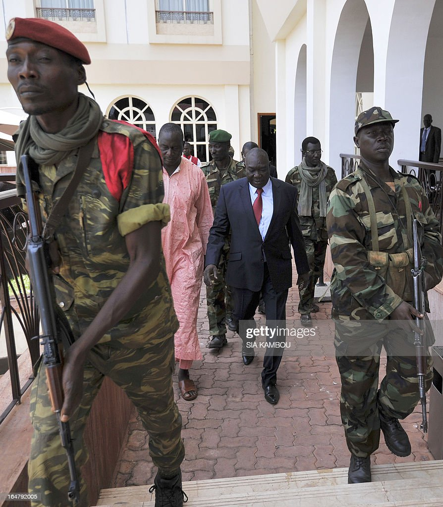 The Central African Republic's new strongman, Michel Djotodia (C) walks out after a meeting with Central African Seleka rebels, whose coalition on March 24, 2013 seized control of Bangui in a rapid-fire weekend assault that forced President Francois Bozize into exile, and Central African Republic Army Forces (FACA) soldiers on March 28, 2013 in Bangui. New rebel authorities in the Central African Republic struggled to restore order in the coup-hit capital on Thursday as the UN warned tens of thousands of people faced going hungry after days of looting.