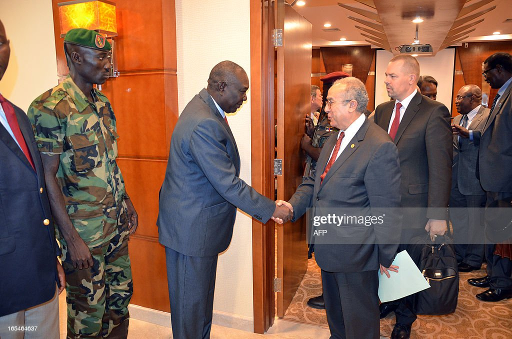 The Central African Republic's rebel strongman and self-proclaimed President Michel Djotodia (2ndL) shakes hands with African Union commissioner for Peace and Security, Ramtame Lamamra (2ndR) on April 4, 2013 in Bangui. Djotodia has accepted the outcome of a regional summit on the country's crisis, which called for the election of a new interim president following last month's coup, Prime Minister Tiangaye said today. Leaders at the summit refused to accept Djotodia's role as self-proclaimed president of the poor and strife-torn country after the ouster of elected president Francois Bozize by his rebel Seleka coalition almost two weeks ago. AFP PHOTO / PATRICK FORT