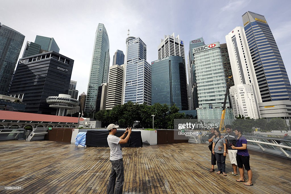 The central business district stands behind a group of people on the waterfront in Singapore, on Saturday, Dec. 29, 2012. Singapore may grapple with elevated inflationary pressures for a third year in 2013, reducing scope for the central bank to provide stimulus to an economy that probably entered a technical recession this quarter. Photographer: Munshi Ahmed/Bloomberg via Getty Images