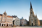 """The central square in Novi Sad, Serbia or The Trg Slobode. Visible are traditional architecture, Parochial Roman Catholic Church of the name of Mary's and the statue of Svetozar Miletic.See more imag"
