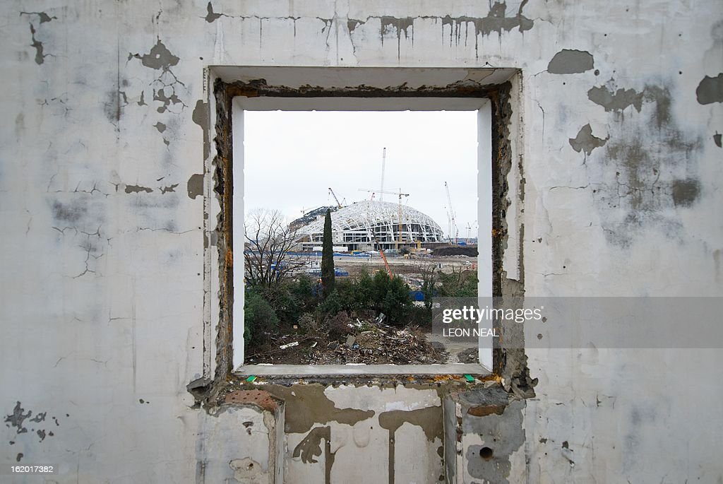 The Central Stadium for the Winter Olympics 2014 is seen through the window of a derelict house in Sochi on February 18, 2013. With a year to go until the Sochi 2014 Winter Games, construction work and development continues as Olympic tests events and World Championship competitions are underway.