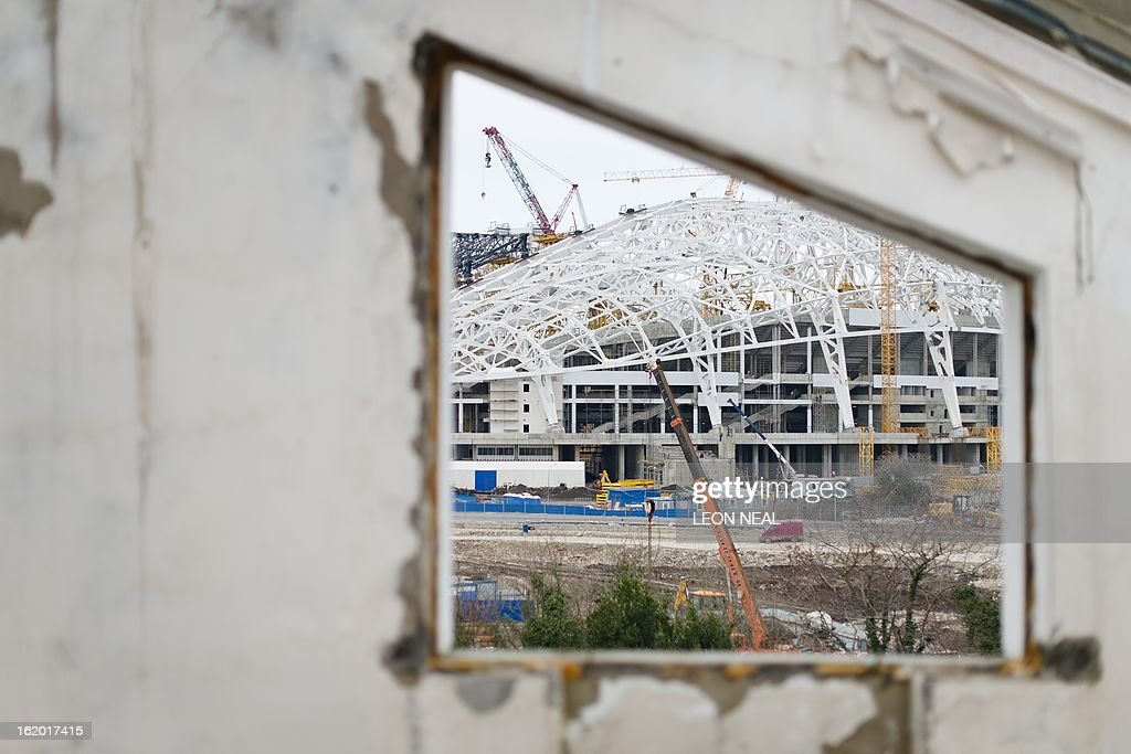 The Central Stadium for the Winter Olympics 2014 is seen through the window of a derelict house in the Sochi district of Adler, on February 18, 2013. With a year to go until the Sochi 2014 Winter Games, construction work and development continues as Olympic tests events and World Championship competitions are underway.