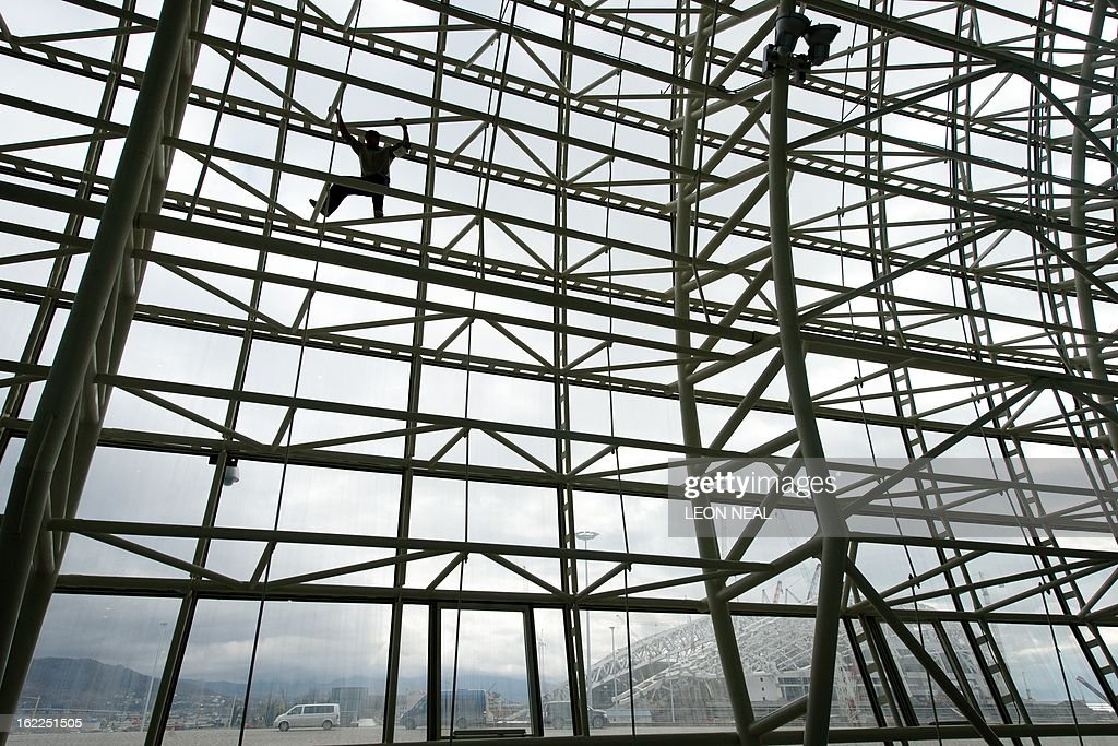 The Central Stadium is visible in the distance as a construction worker climbs up the structural framework of the Bolshoi Ice Palace in the Olympic Park in Adler, Russia on February 21, 2013. With a year to go until the Sochi 2014 Winter Games, construction work continues as tests events and World Championship competitions are underway. AFP PHOTO / LEON NEAL