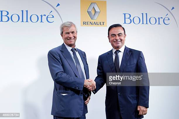 The CEO of French carmaker Renault Carlos Ghosn shakes hands with French industrial group Bollore's head Vincent Bollore at the end of a press...