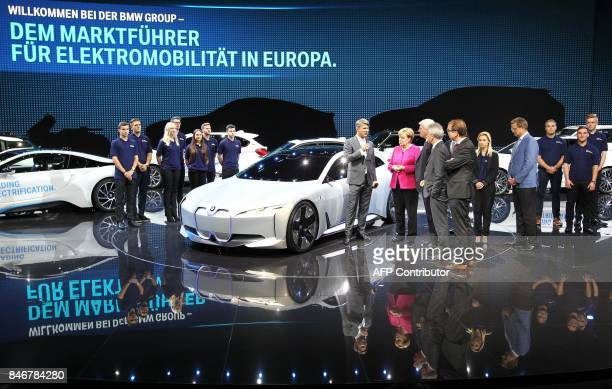 The CEO of German car maker BMW Harald Krueger shows a BMW car to German Chancellor Angela Merkel as she visits the booth of BMW during the official...