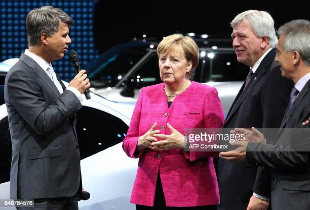 The CEO of German car maker BMW Harald Krueger talks with German Chancellor Angela Merkel and Hesse's State Premier Volker Bouffier as they visit the...