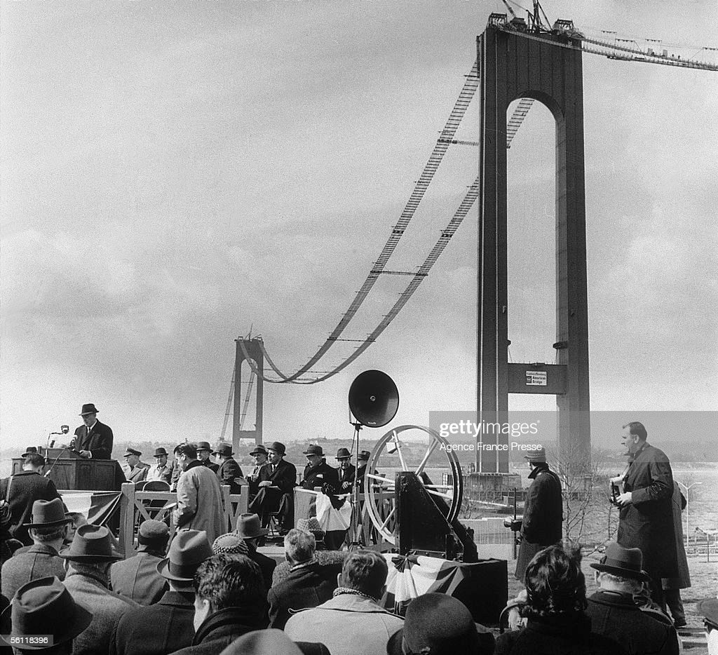 The ceremony marking the beginning of the spinning of the steel cables for the Verrazano Bridge, which links Brooklyn and Staten Island, New York. The bridge was completed in 1964.