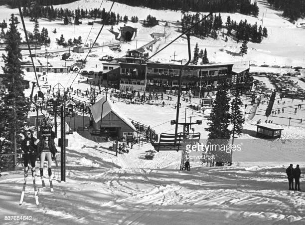 The chairlift at the left brings skiers up the slope in this view looking down at the facilities in the valley at the Winter Park ski area At top...